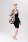 Beautiful business woman blonde in black dress, jacket and purs Royalty Free Stock Photos