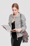 Beautiful business woman blonde in black dress, jacket reading a magazine on gray background Stock Photo