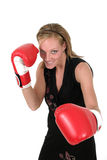 Beautiful Business Woman In Boxing Gloves 1. Attractive blonde executive business woman puts on the boxing gloves to do battle in the corporate world stock photo