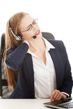 Beautiful business woman at call center is having back ache. Royalty Free Stock Image
