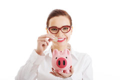 Beautiful business woman with coin and piggy- bank. Royalty Free Stock Images