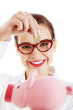 Beautiful business woman with coin and piggy- bank. Stock Photos