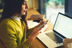 Beautiful business woman with dark hair and yellow sweater works in coworking. Charming young female student having break for chatting in social networks via Stock Images