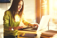 Beautiful business woman with dark hair and yellow sweater works in coworking. Concentrated attractive brunette author of popular publication working on book Royalty Free Stock Image