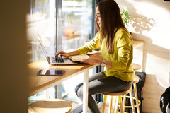 Beautiful business woman with dark hair and yellow sweater works in coworking Royalty Free Stock Images