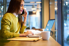 Beautiful business woman with dark hair and yellow sweater works in coworking connected to free wireless internet Royalty Free Stock Photography