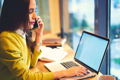 Beautiful business woman with dark hair and yellow sweater works in coworking connected to free wireless internet. Concentrated young female content manager of Stock Photography