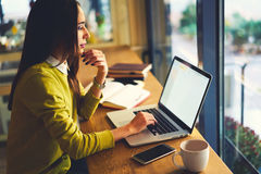 Beautiful business woman with dark hair and yellow sweater works in coworking. Professional female graphic designer modeling outlay using application on laptop Royalty Free Stock Photos
