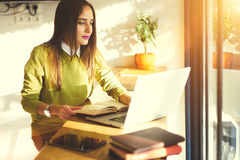 Beautiful business woman with dark hair and yellow sweater works in coworking using application on laptop computer Stock Photo
