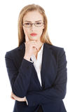 Beautiful business woman in eyeglasses with finger on her cheek. Royalty Free Stock Photos
