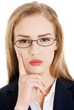 Beautiful business woman in eyeglasses with finger on her cheek. Royalty Free Stock Image