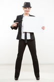 Beautiful business woman with gun olding a blank billboard. Stock Image