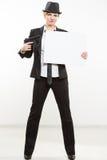 Beautiful business woman with gun olding a blank billboard. Stock Photo
