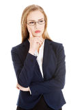 Beautiful business woman with her finger on cheek thinking. Royalty Free Stock Photography
