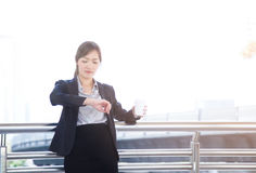 Beautiful business woman holding a cup of coffee and checking th Stock Images