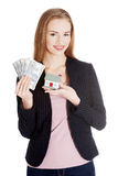 Beautiful business woman holding dollar currency and house. Royalty Free Stock Images