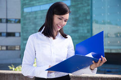 Beautiful business woman holding folder with documents. Young beautiful business woman holding folder with documents stock images