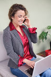 Beautiful business woman holding laptop talking on cellphone Royalty Free Stock Photos