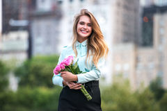 Beautiful business woman holding roses flowers bouquet and smiling in the city. Beautiful business woman holding roses flowers boquet and smiling in the city Stock Images