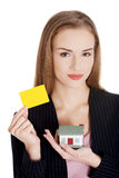 Beautiful business woman holding small house and personal card. Stock Images