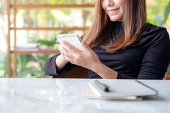 A beautiful business woman holding and writing on notebook in cafe with green nature background. Closeup image of a beautiful business woman holding and writing stock photography