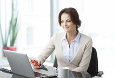 Beautiful business woman with laptop. Portrait of a beautiful business woman sitting in the office Royalty Free Stock Photos