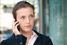 Beautiful business woman listening to phone call on mobile. Close up portrait of a beautiful business woman listening to phone call on mobile Royalty Free Stock Image