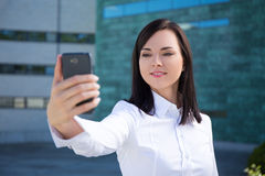 Beautiful business woman making selfie photo on smartphone Royalty Free Stock Photo
