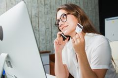 Beautiful business woman at office credit card online commerce. Looking at computer monitor. Casual look, internet shopping Royalty Free Stock Image