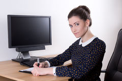Beautiful business woman in office using computer with empty mon Stock Photography