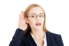 Beautiful business woman is over- hearing, trouching her ear. stock images