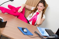 Beautiful business woman in a pink tie at the tabl Stock Photography