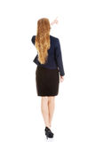 Beautiful business woman pointing up. Rear view. Isolated on white Stock Photography