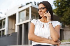 Beautiful business woman posing outdoors at the street talking by phone. Image of a beautiful business woman posing outdoors at the street talking by phone stock images