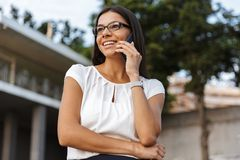 Beautiful business woman posing outdoors at the street talking by phone. Image of a beautiful business woman posing outdoors at the street talking by phone royalty free stock photography