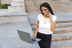 Beautiful business woman posing outdoors at the street using laptop computer talking by phone. Image of a beautiful business woman posing outdoors at the street stock image