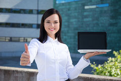 Beautiful business woman showing laptop with blank screen and th Stock Photos