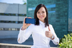 Beautiful business woman showing smartphone with blank screen Stock Image