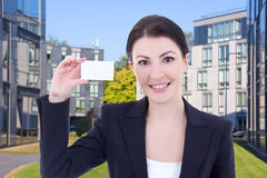 Beautiful business woman showing visiting card on street against Royalty Free Stock Image