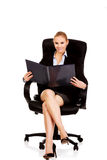 Beautiful business woman sitting on armchair and reading notes Stock Image