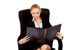 Beautiful business woman sitting on armchair and reading notes Stock Photo