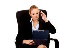 Beautiful business woman sitting on armchair and reading notes Stock Photos