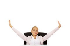 Beautiful business woman sitting behind the desk and stretching her arms Stock Photos