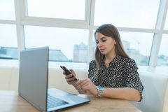 Beautiful business woman sitting in a cafe near a laptop and using a smartphone. Royalty Free Stock Image