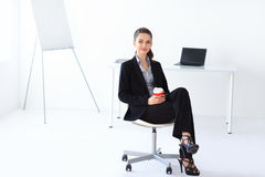 Beautiful business woman sitting on chair with cup of coffee in Royalty Free Stock Image