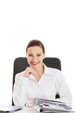 Beautiful business woman sitting by a desk. Stock Photos