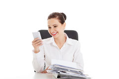 Beautiful business woman sitting by a desk with stack of papers. Stock Photo