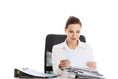Beautiful business woman sitting by a desk. Royalty Free Stock Images