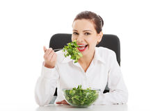 Beautiful business woman sitting and eating lettuce. Isolated on white stock images