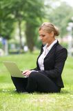 Beautiful business woman sitting with laptop in park Stock Photo